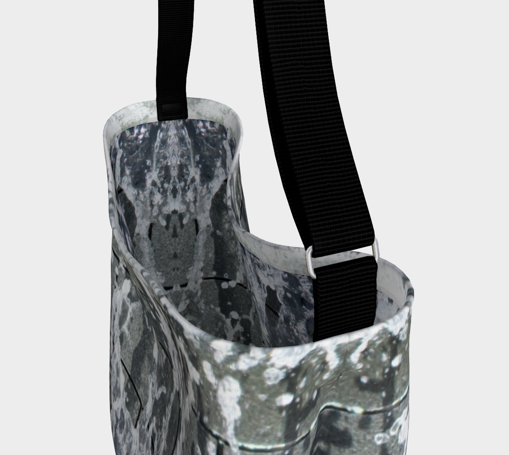 Close up view of black strap and inside of tote with gray, white and black design depicting running water
