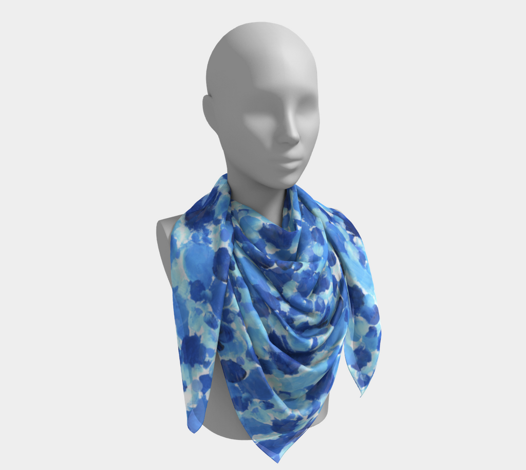 Scarf worn on mannequin with design of splotches of light blue, medium blue, and dark blue on a white background give an impression of bubbles.