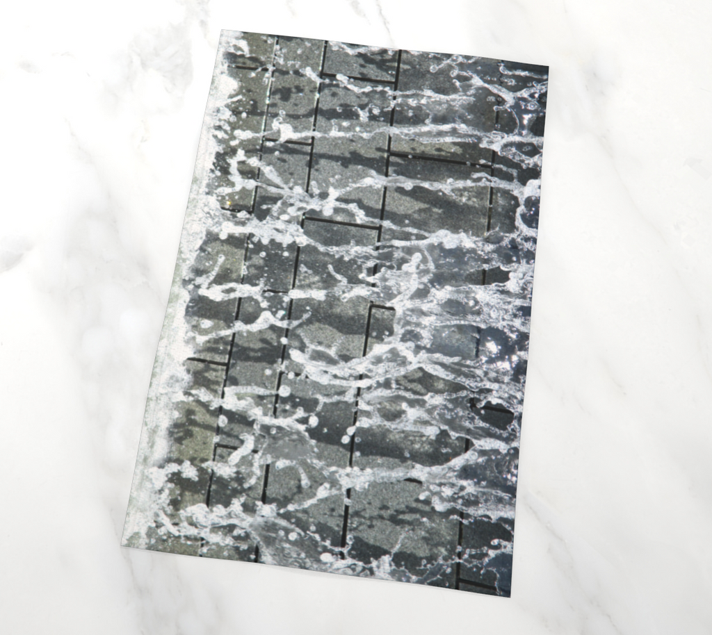 Flat lay view of tea towel with gray, white and black design depicting running water