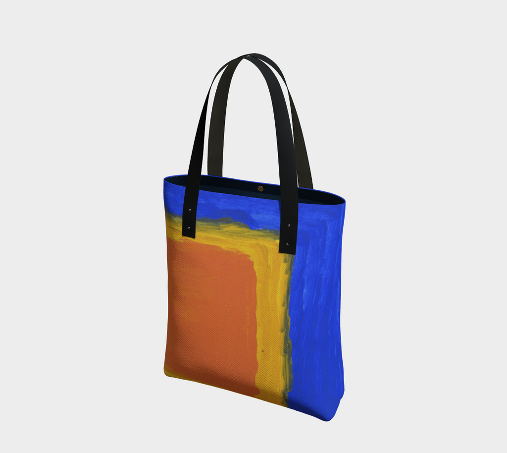 Lined tote bag with magnet clasp and vegan leather black straps. The pattern is a blue background and large yellow and orange square in lower right hand corner