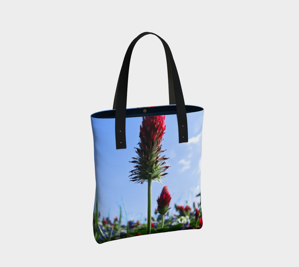 Tote bag with black double straps showing Red Indian paintbrush flowers and bluebonnets in a green field