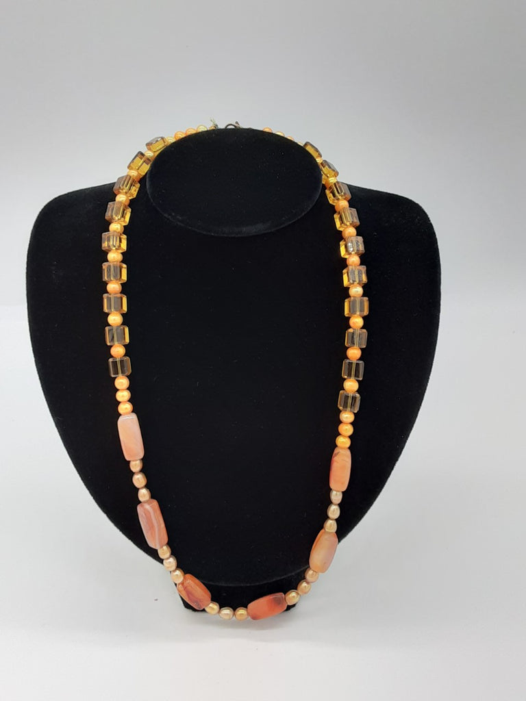 Orange necklace with a variety of bead shapes. Around the neck- clear yellow/orange cubes  and round opaque beads. In the center- gold glass oval pearls and cylinders of agate