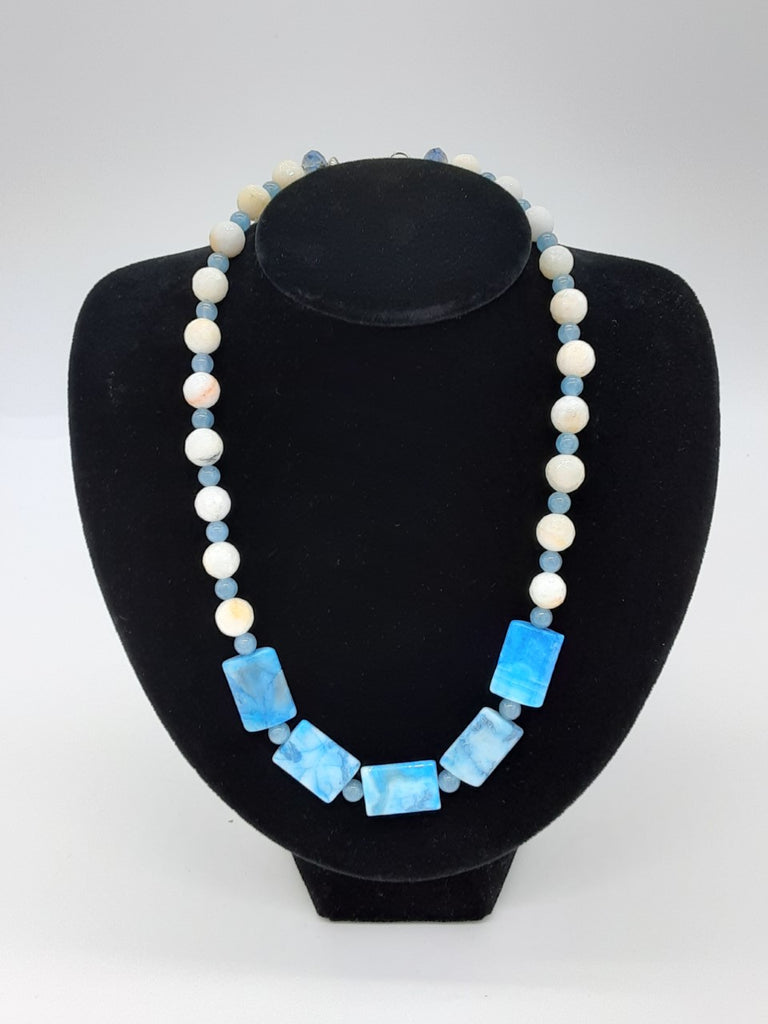 alternating light blue and white beads around most of the necklace. the center has 5 larger rectangle light blue marbled beads