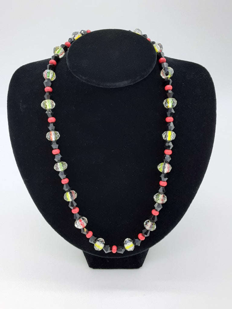 Necklace with pattern of beads alternating: clear glass, black, red, black, and clear glass