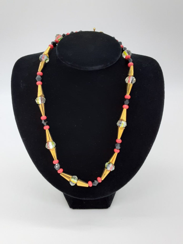 necklace of repeating beads- black, red, gold cone shaped, glass, gold cone shaped, red, and black beads