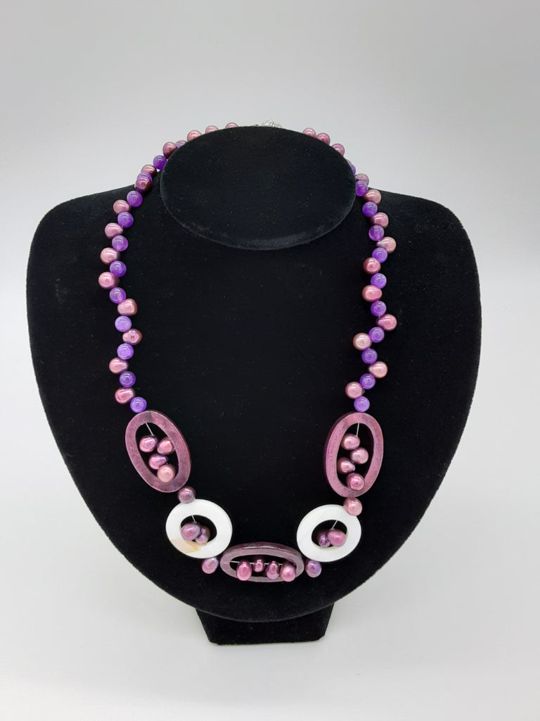 Necklace of purples- alternating with pearl and transparent purple, in the center has oval shapes with the pearls inside