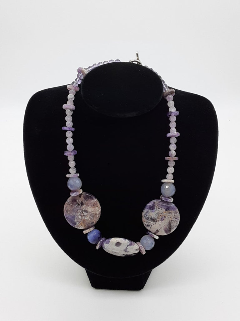 necklace made with purple quartz. Mostly round beads with a a few disks. The center has three large flat beads of purple and white pattern