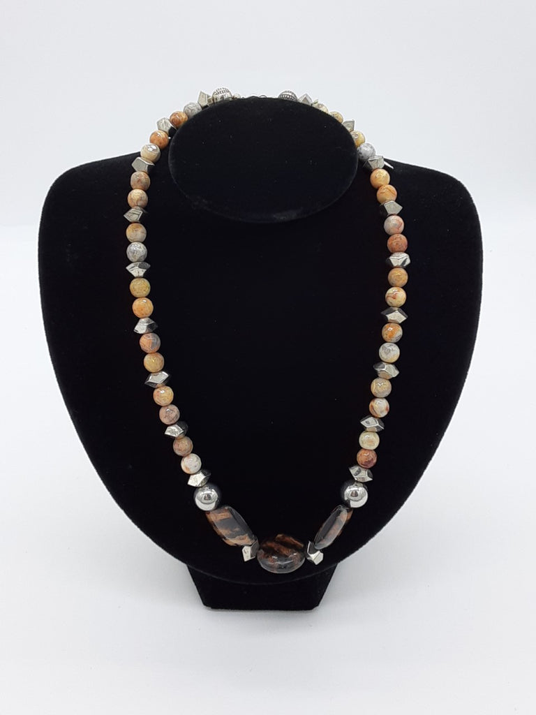 Necklace of beiges , with three tiger striped beads in the center- alternating silver