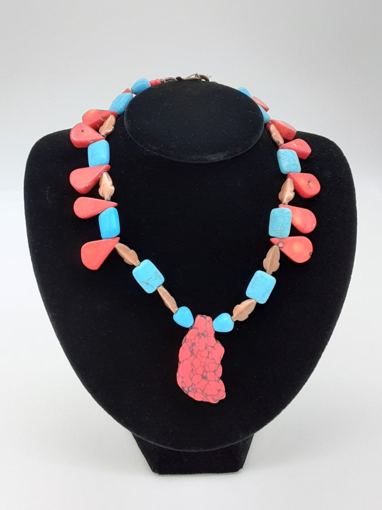 Necklace alternating in turquoise square beads, coral flat tear dropped shaped beads, copper shaped leaves. There is a large center pendant of an irregular cut red and black stone