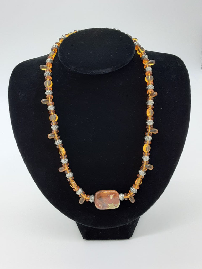 Necklace that is mostly light browns with some silver and a large semi precious gem stone in the center