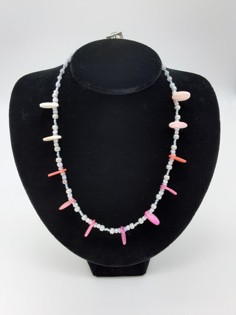 Necklace of small pale beads with circular disks of pearl in between- the color pearl is white, coral, and pink