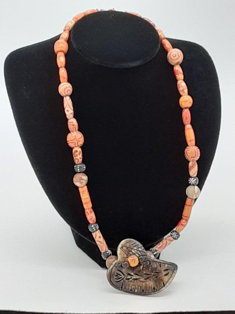 necklace with Orange decorative patterned wooden beads with a large dark brown carved center piece