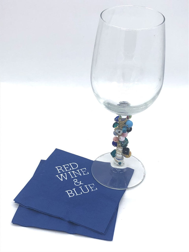Blue napkins with white Red Wine & Blue slogan underneath wine glass