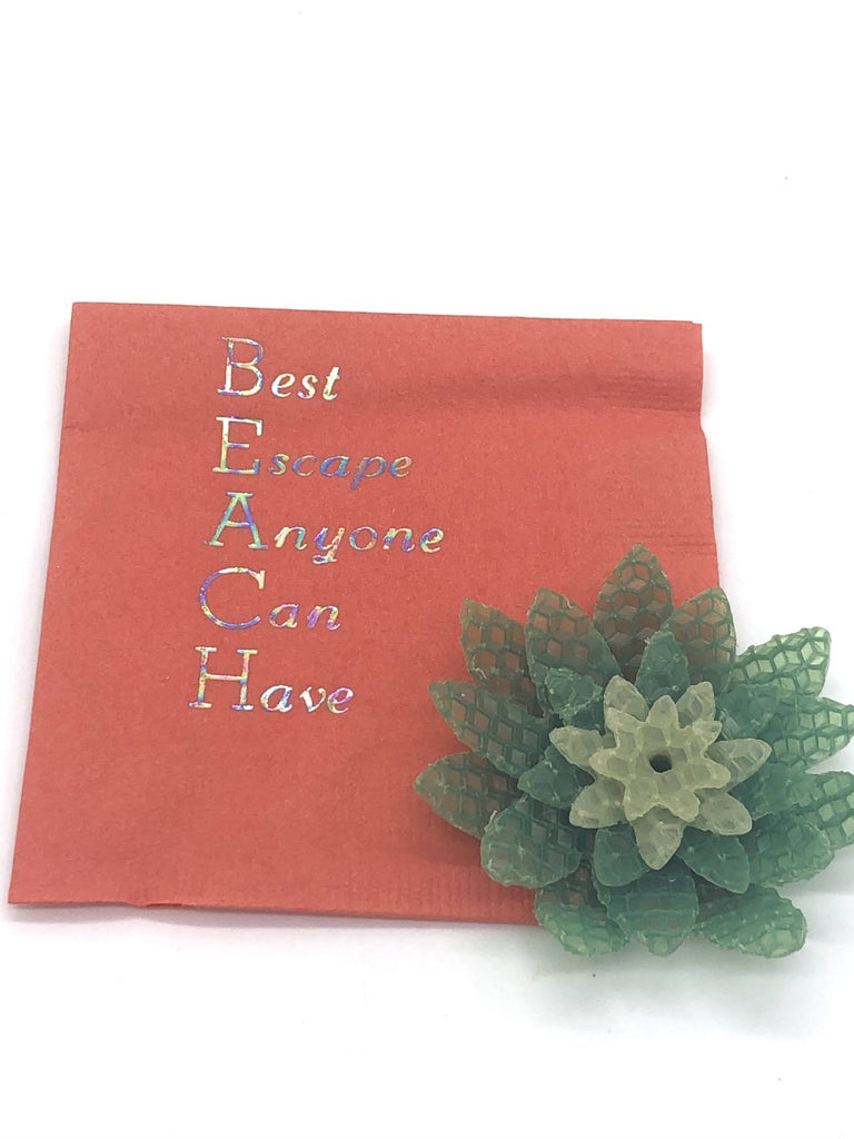 Coral cocktail napkins with iridescent Best Escape Anyone Can Have slogan.  The first letter of each word spells the word BEACH vertically