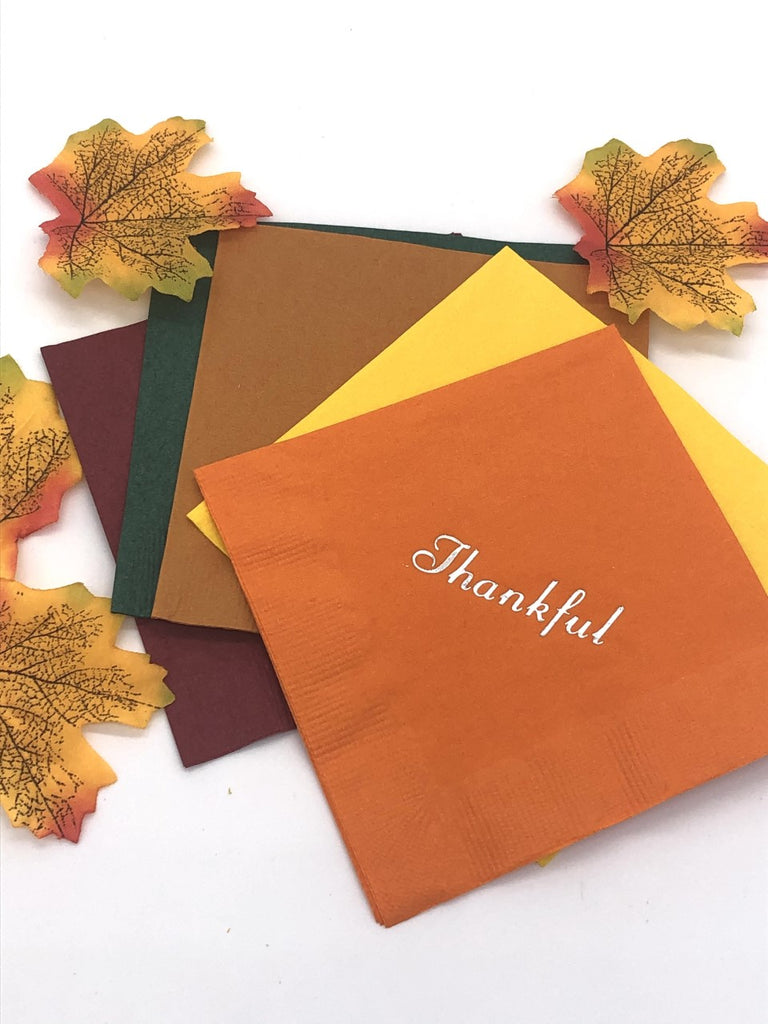 Cocktail napkins in maroon, dark green, light brown, yellow and orange.  The orange napkin has a silver Thankful slogan