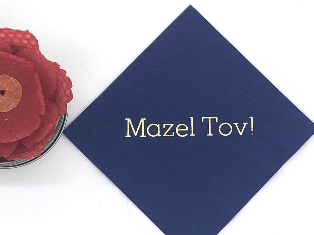 Blue cocktail napkin with gold Mazel Tov! slogan
