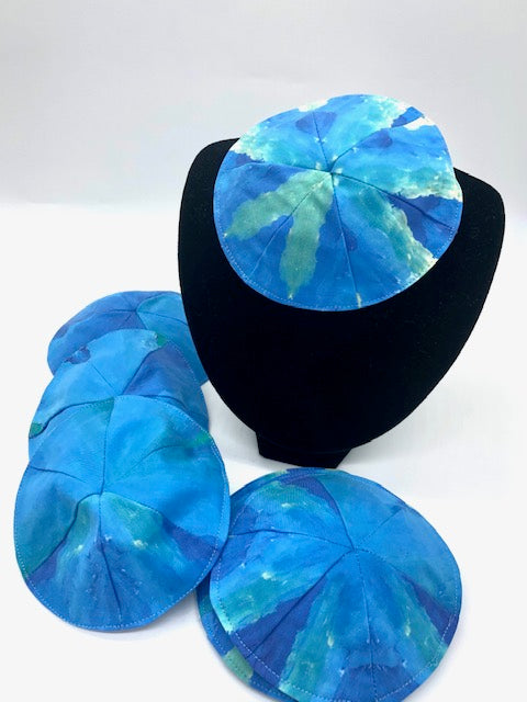 several blue and green striped kippot, one on a velvet stand