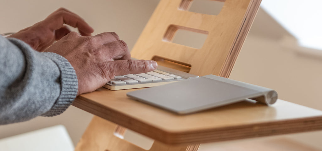 man's hand writing on keyboard