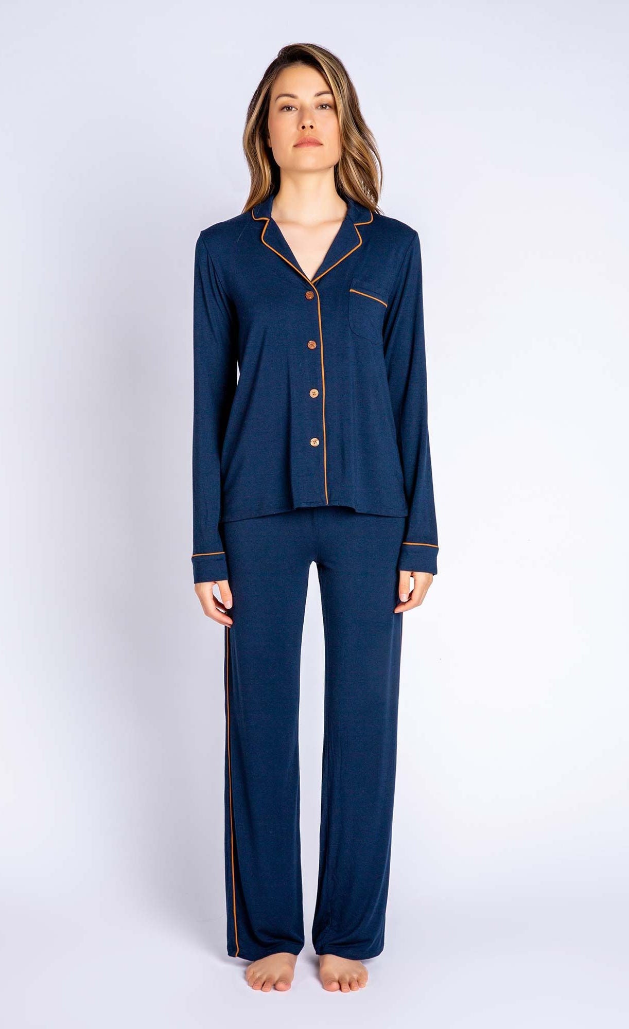 Front angle of woman wearing matching navy pj top and pj bottom from PJ Salvage