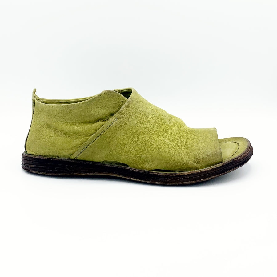 Outer side view of the as98 reiley flat sandal in a green detox color. The shoe in this image covers the foot in leather that layers over on the side. The shoe has an open toe.