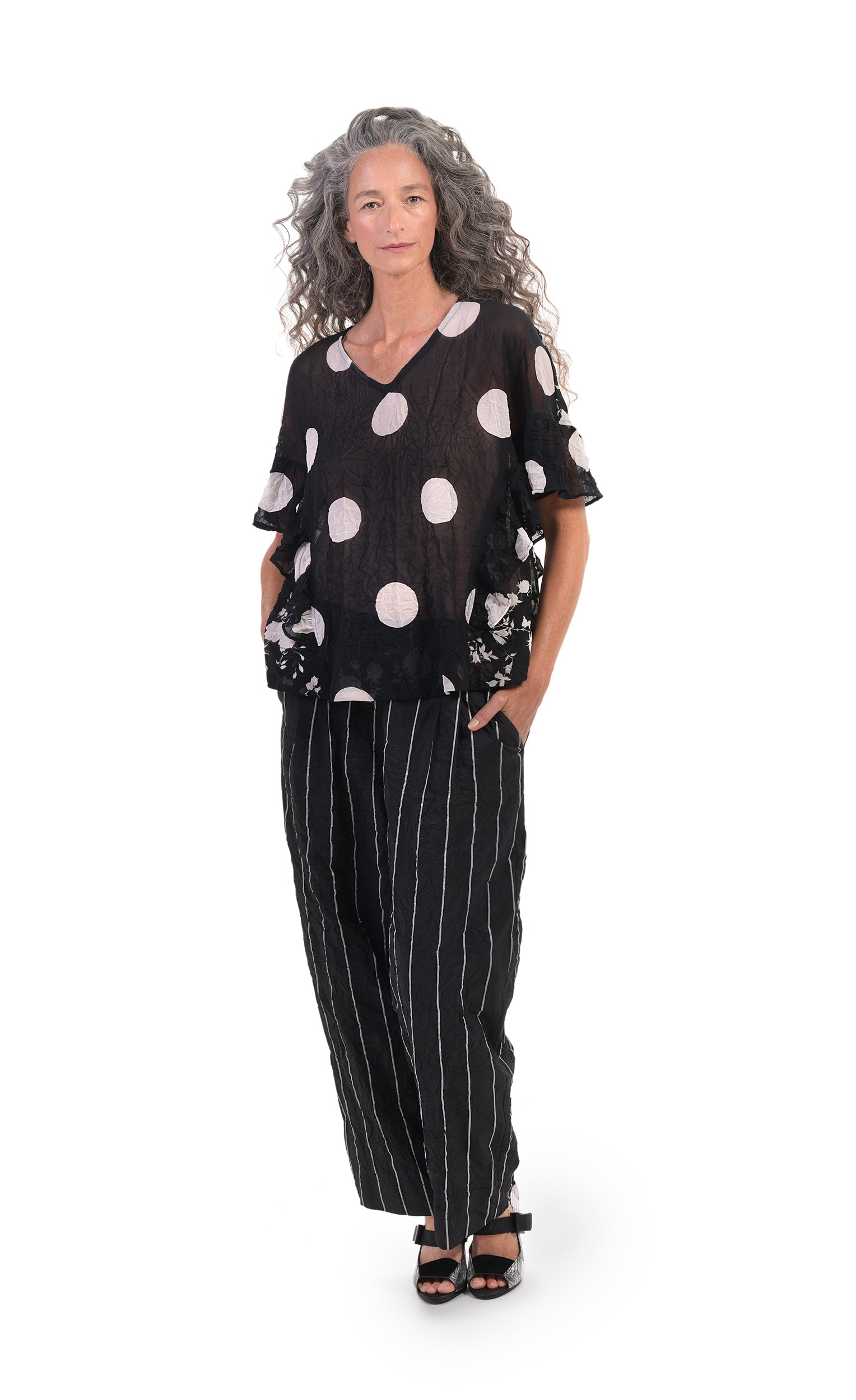 Front full body view of a woman wearing the alembika pinstriped pant with a black and white dotted top. The pant is black with white pinstripes. The front has two slanted pockets on the side. The waist is elastic and the pant sits right at the ankles. This pant has a straight leg silhouette.