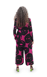 Back full body view of a woman wearing the Alembika art print palazzo pant with a matching art print jacket. The pant has a wide leg that ends right above the ankle. It is magenta/violet colored with a black swirl print.