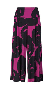 Front view of the Alembika art print palazzo pant. The pant has a wide leg that ends right above the ankle. It is magenta/violet colored with a black swirl print.