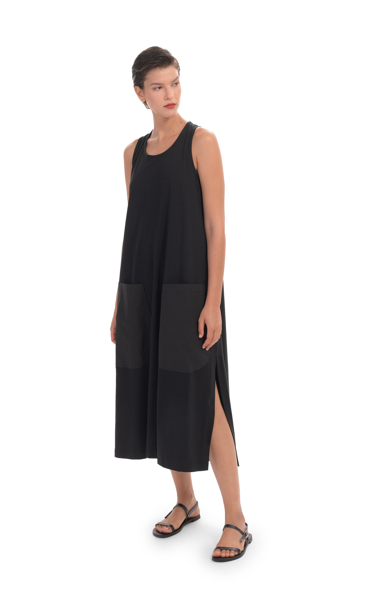 Front full body view of a woman wearing the alembika cotton tank dress. This black dress is sleeveless with two large patch pockets on the front and long side slits. This dress goes down to just below the model's knees.