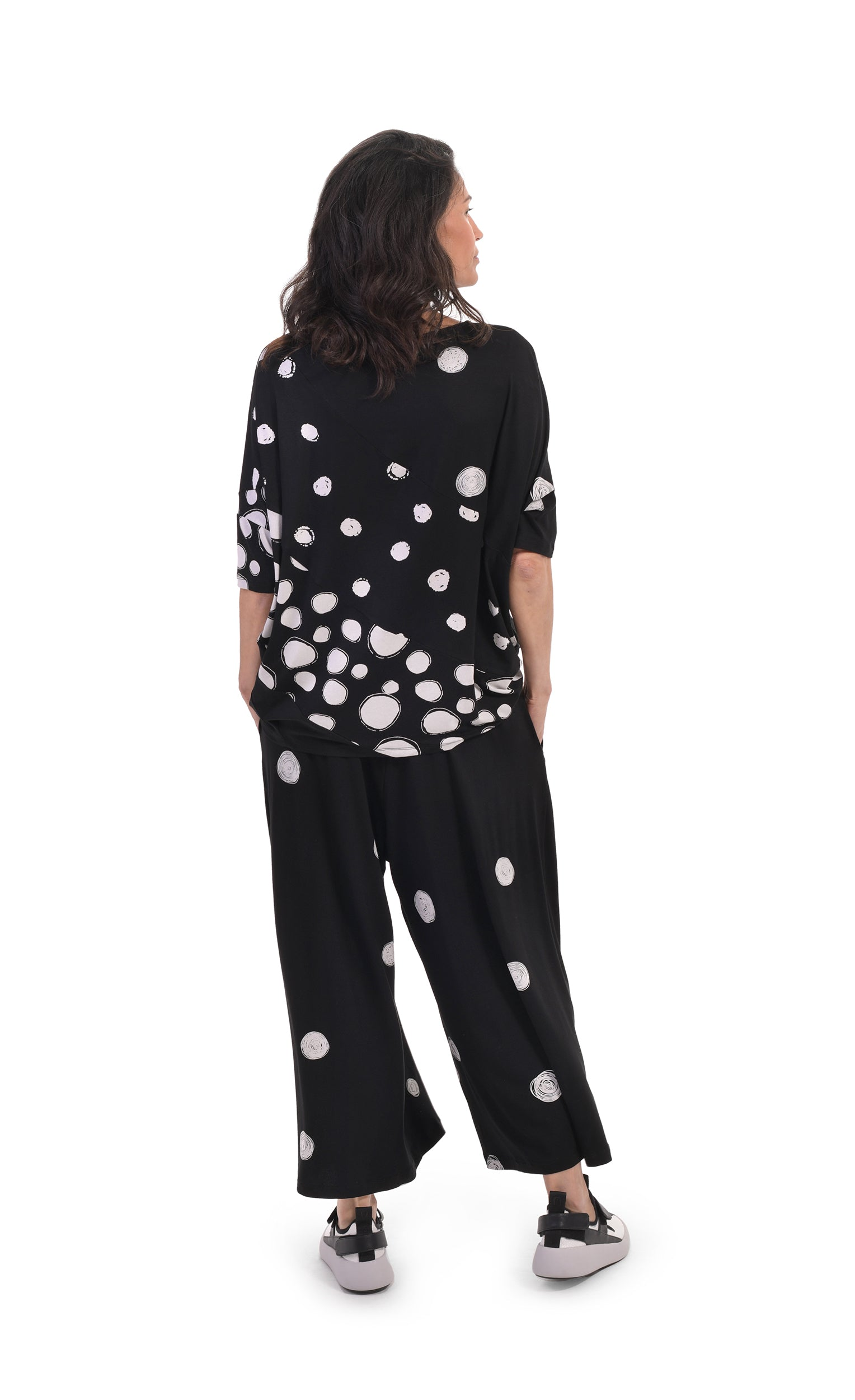Back, full body view of a woman wearing the alembika multi spotted lia jersey top. This top is black with different types of white spots all over it. The sleeves are 3/4 length and the shirt has an oversized fit. On the bottom she is wearing full leg black pants with white dots.