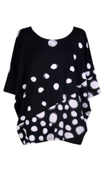 Load image into Gallery viewer, Front view of the alembika multi spotted lia jersey top. This top is black with different types of white spots all over it. The sleeves are 3/4 length and the shirt has an oversized fit.