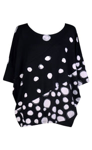 Front view of the alembika multi spotted lia jersey top. This top is black with different types of white spots all over it. The sleeves are 3/4 length and the shirt has an oversized fit.