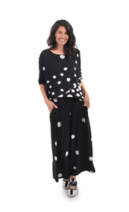 Front full body view of a woman wearing the alembika multi spotted lia jersey top. This top is black with different types of white spots all over it. The sleeves are 3/4 length and the shirt has an oversized fit.
