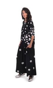 Front, left sided, full body view of a woman wearing the alembika multi spotted lia jersey top. This top is black with different types of white spots all over it. The sleeves are 3/4 length and the shirt has an oversized fit. On the bottom she is wearing full leg black pants with white dots.
