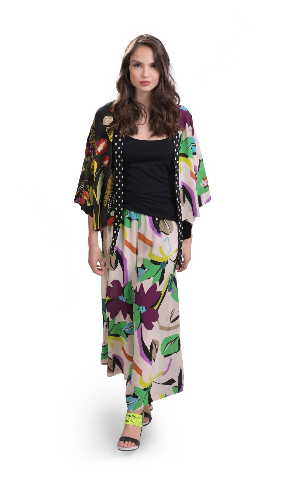 Front full body view of a woman wearing the alembika floral mix print kimono. This kimono has a dark jungle print on the right side and a light jungle print on the left. The attached shawl collar is black with white dots. This kimono has an open front and drop shoulder kimono sleeves that end at the elbows. On the bottom, the woman is wearing the jungle print bottoms.