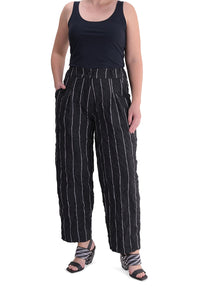 Front bottom half view of a woman wearing the alembika pinstriped pant. This pant is black with white pinstripes. The front has two slanted pockets on the side. The waist is elastic and the pant sits right at the ankles. This pant has a straight leg silhouette.