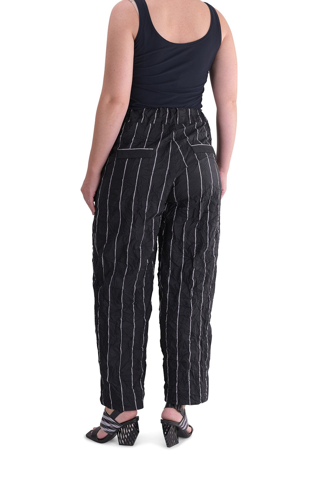 Back bottom half view of a woman wearing the alembika pinstriped pant. The pant is black with white pinstripes. The back has two welt pockets.  The waist is elastic and the pant sits right at the ankles. This pant has a straight leg silhouette.