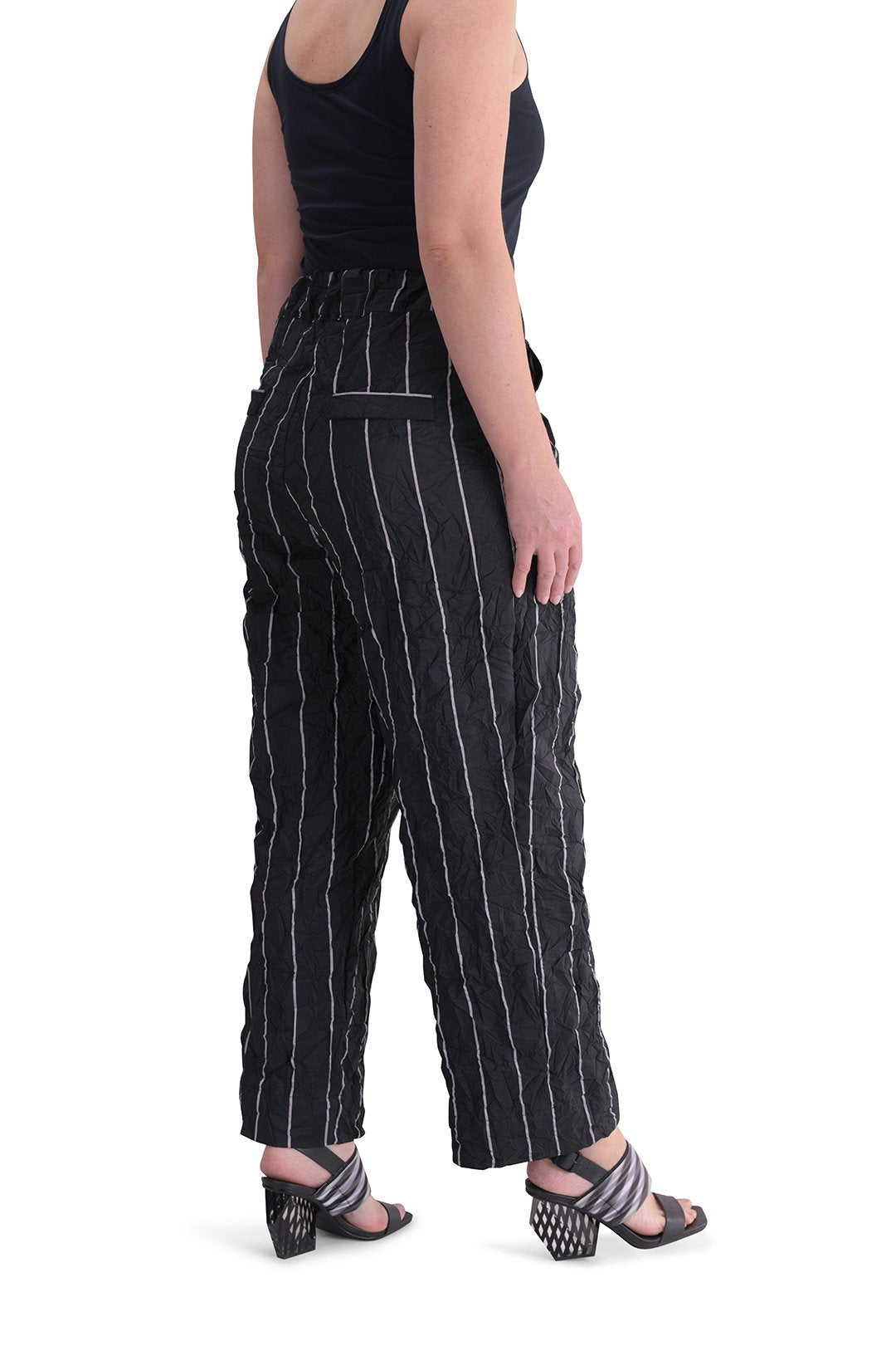 Back, right sided, bottom half view of a woman wearing the alembika pinstriped pant. The pant is black with white pinstripes. The back has two welt pockets. The waist is elastic and the pant sits right at the ankles. This pant has a straight leg silhouette.