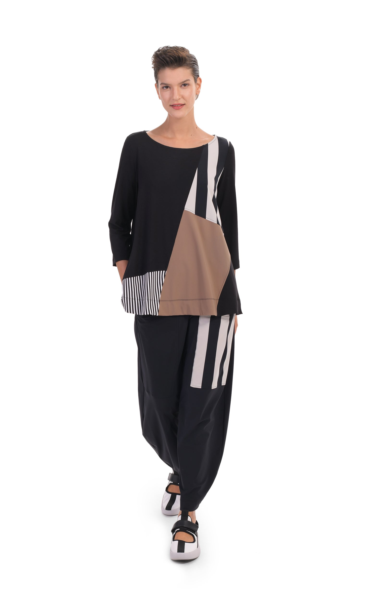 Front full body view of a woman wearing the alembika tekbika mixed print top. This top has 3/4 length sleeves and blocking of black and white stripes and mocha colored patches. On the bottom she is wearing a wide leg pant with a black and white striped patch.