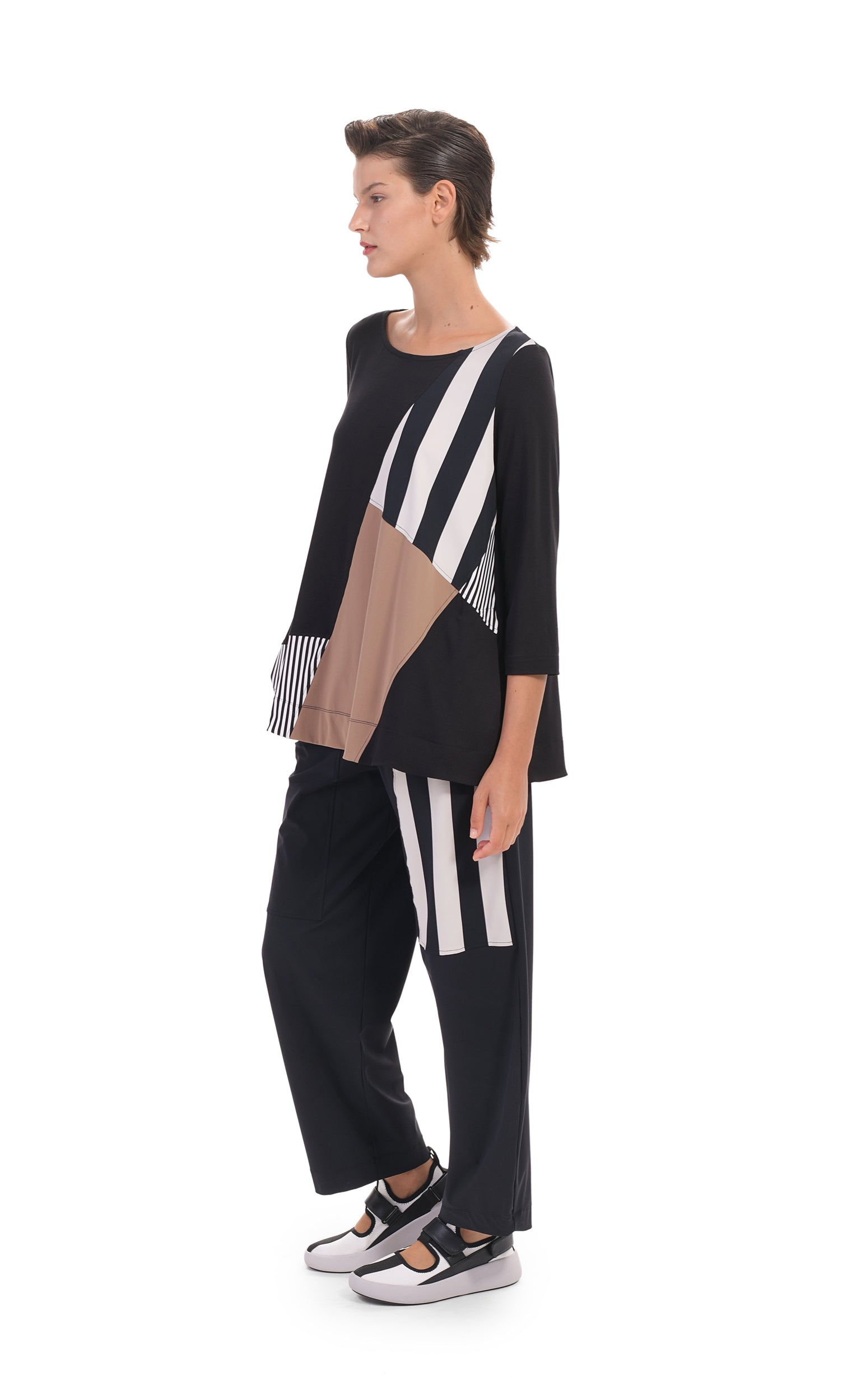 Front, left side full body view of a woman wearing the alembika tekbika mixed print top. This top has 3/4 length sleeves and blocking of black and white stripes and mocha colored patches. On the bottom she is wearing a wide leg pant with a black and white striped patch.