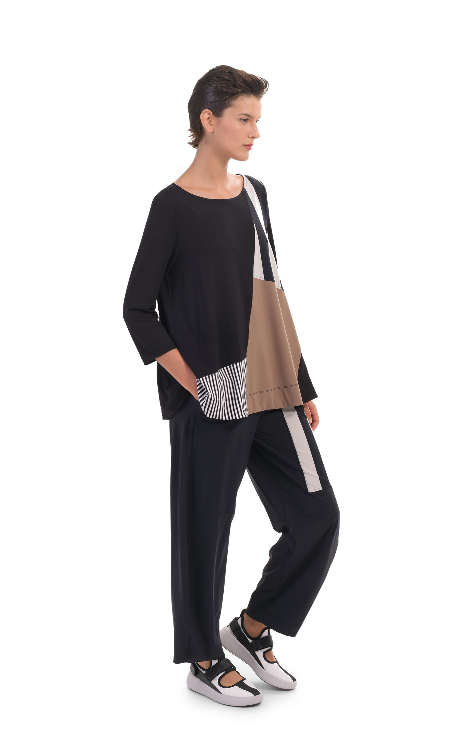 Front, left full body view of a woman wearing the alembika tekbika mixed print top. This top has 3/4 length sleeves and blocking of black and white stripes and mocha colored patches. On the bottom she is wearing a wide leg pant with a black and white striped patch.