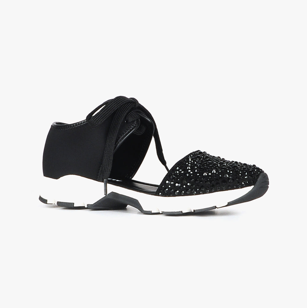 Outer side view of the All Black amazing gems sneaker sandal. This sneaker sandal has a lace up front separated from the toe upper. The upper on the toe is decorated with black rhinestones