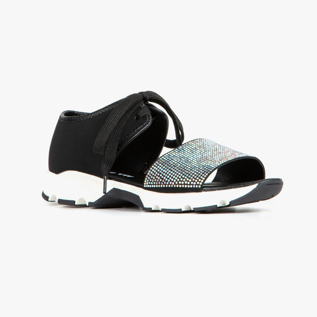 Right side view of the all black banded pave sneaker sandal. This sneaker sandal has a black upper with a shoe lace closure. The upper near the ankle is cut off from the upper that covers the toes. The upper on the toes is detailed with white rhinestones. The shoe is black and white and the front is open toed.