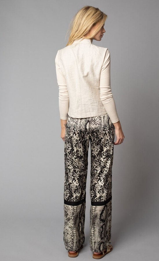 Back, full body view of a woman wearing a beige jacket with fitted sleeves. On the bottom-half, she is wearing the Lola & Sophie Animal Border Print Pull-On Pant. These pants feature a smudge print and a snake print separated by a back stripe that runs horizontally across the leg near the knee. These relaxed, straight pants have a side slit that goes up to the knee.