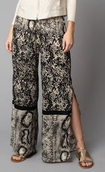 Load image into Gallery viewer, Front, bottom half view of a woman wearing the Lola & Sophie Animal Border Print Pull-On Pant. These pants feature a smudge print and a snake print separated by a back stripe that runs horizontally across the leg near the knee. These relaxed, straight pants have a side slit that goes up to the knee.