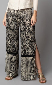 Front, bottom half view of a woman wearing the Lola & Sophie Animal Border Print Pull-On Pant. These pants feature a smudge print and a snake print separated by a back stripe that runs horizontally across the leg near the knee. These relaxed, straight pants have a side slit that goes up to the knee.