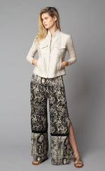 Load image into Gallery viewer, Front, full body view of a woman with her hands in the front pockets of the beige button up jacket she is wearing. On the bottom-half, she is wearing the Lola & Sophie Animal Border Print Pull-On Pant. These pants feature a smudge print and a snake print separated by a back stripe that runs horizontally across the leg near the knee. These relaxed, straight pants have a side slit that goes up to the knee.
