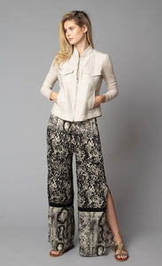 Front, full body view of a woman with her hands in the front pockets of the beige button up jacket she is wearing. On the bottom-half, she is wearing the Lola & Sophie Animal Border Print Pull-On Pant. These pants feature a smudge print and a snake print separated by a back stripe that runs horizontally across the leg near the knee. These relaxed, straight pants have a side slit that goes up to the knee.