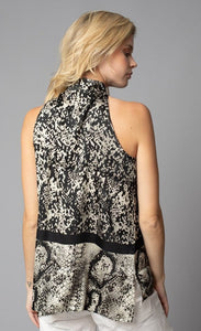 Back, top half view of a woman wearing the lola & sophie border animal print halter top. This sleeveless top has a high halter neck and a mix of two different snake skin prints separated by a black border that runs horizontally across the waist. There is also a short zipper on the back of the neck.