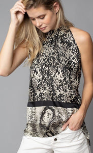 Front, top half view of a woman with one hand in her hair and her left hand in the left pocket of her white shorts. On the top, the woman is wearing the lola & sophie border animal print halter top. This sleeveless top has a high halter neck and a mix of two different snake skin prints separated by a black border that runs horizontally across the waist.
