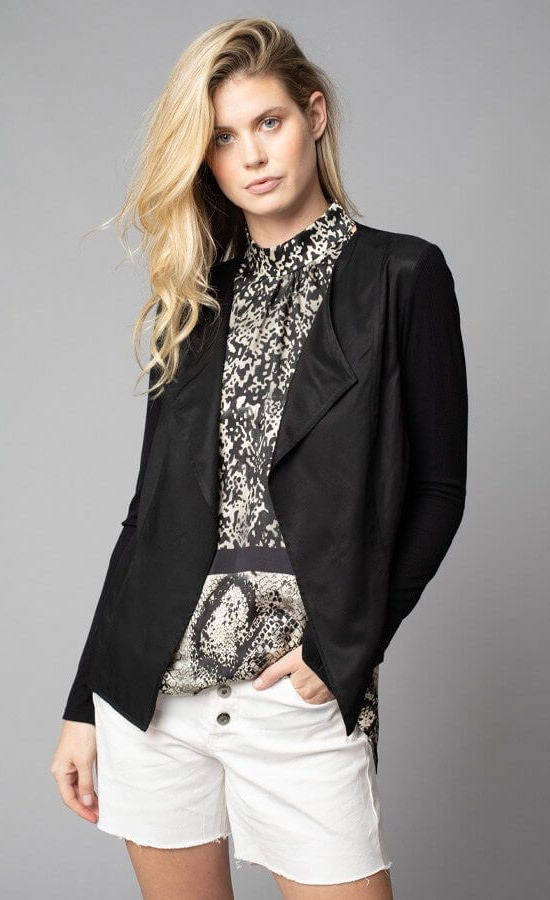 Front, top half view of a woman with her left hand in the left pocket of her white shorts. On the top, the woman is wearing the lola & sophie black Crinkle Linen Zip-Front Long Jacket over the lola & sophie border animal print halter top. The tank underneath has a high halter neck and a mix of two different snake skin prints separated by a black border that runs horizontally across the waist.